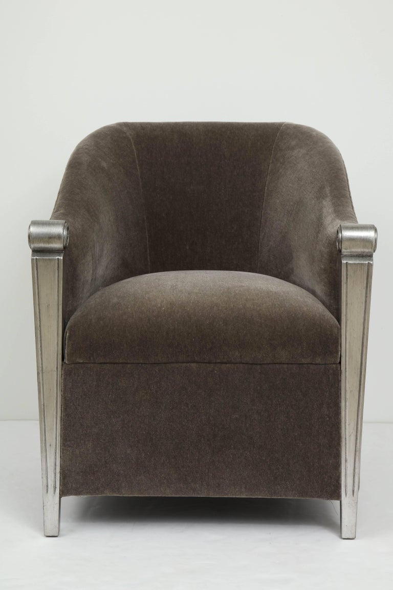 Stunning pair of aged silver leaf framed club chairs with new plush, medium grey mohair upholstery. Chairs have a barrel back silhouette and two splayed back legs. Chairs are in mint restored condition.