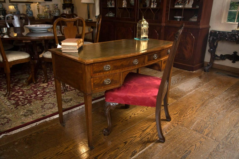 English mahogany bow front writing table / desk, circa 1905, with green hand-tooled leather writing surface and mahogany border with boxwood and mahogany string inlay. Four bow front drawers feature two long drawers over two short drawers with each