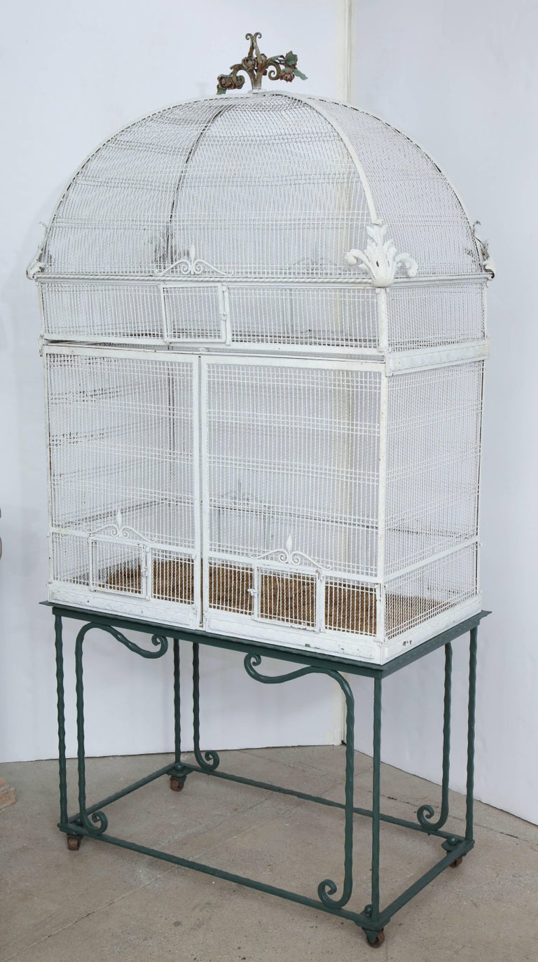 A large white painted birdcage on a metal stand.