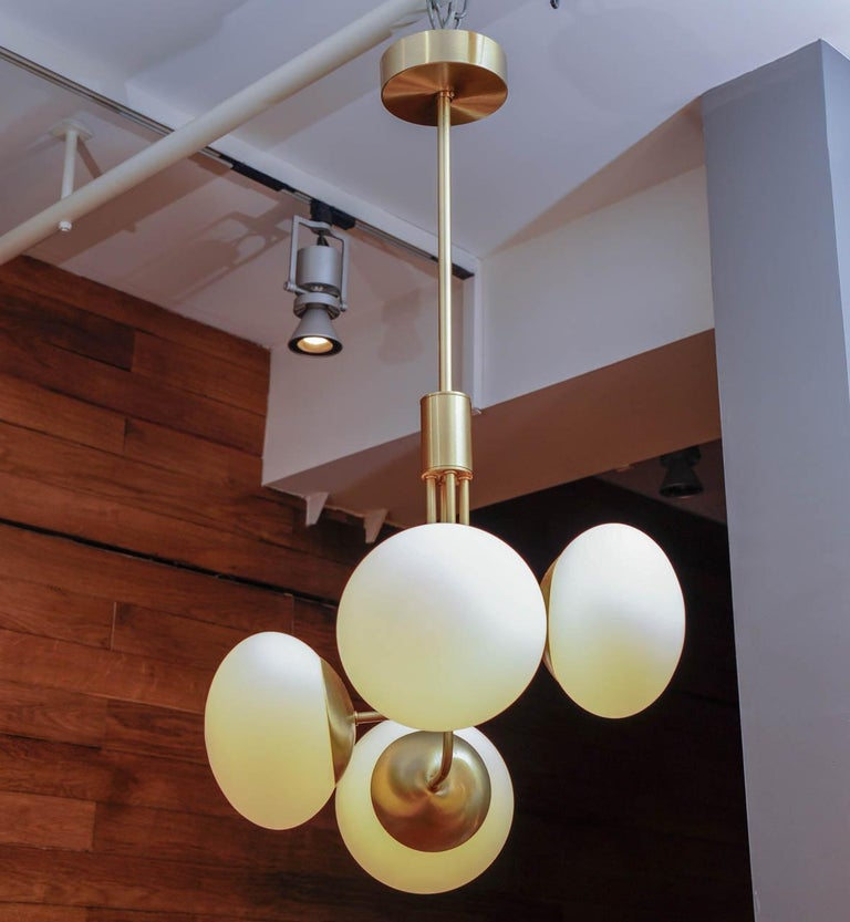 Nice and elegant suspension made of satin brass, four arms of light with white glass globes.