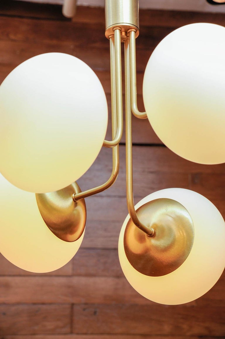 Contemporary Satin Brass Suspension with Four Lights and Round White Glass Globe For Sale