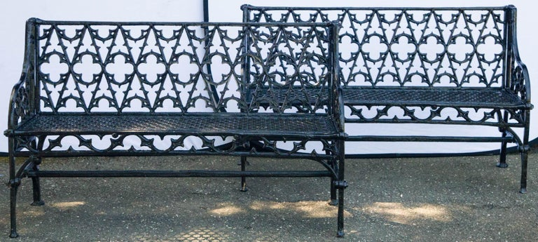 Pair of black Gothic style cast iron garden benches with open work seat and back.
