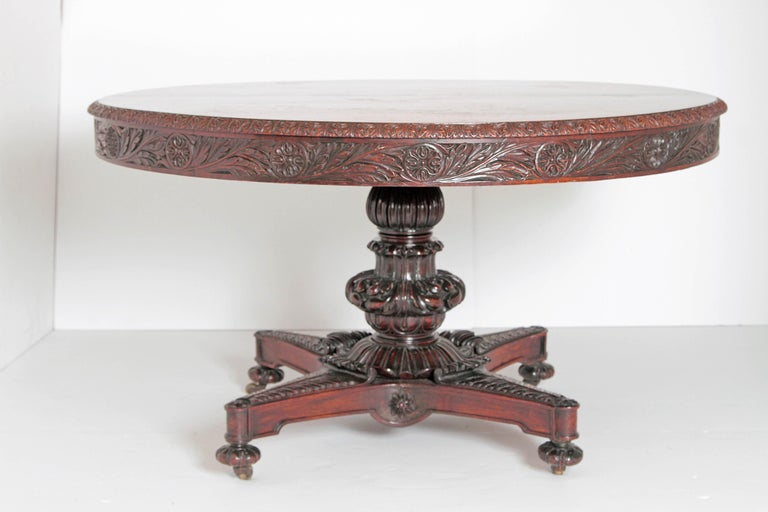 A late 19th century large Anglo-Indian tilt-top, breakfast or centre table with heavily carved foliage and stylized rosettes on rim and apron. Deeply carved pedestal base with four extensions heavily carved in stylized acanthus leaf and bun feet. On