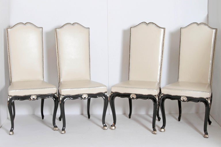 A set of twelve high back dining side chairs Louis XV style with ebonized wood frames with gilt bronze mounts at knees and gilt shell centre front. Gilt hoof feet. Cream leather upholstery with nail-heads.