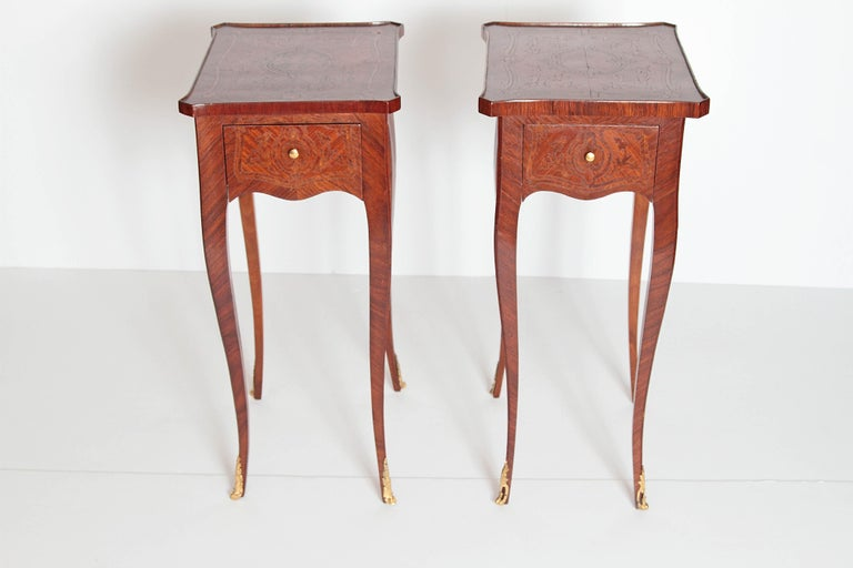 A pair of petite Louis XV Transitional-style side tables of fruitwood with delicately shaped legs and apron with intricate inlaid design on tops and sides. Small single drawer front with candle slide opposite. Slide has embossed and gilded leather