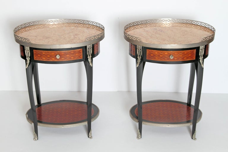 A pair of French Louis XVI-style oval guéridons, occasional or side tables with peach colored stone tops. Silver gilt gallery around top with other silver gilt bronze decorative mounts. Each with single drawer, apron, and lower shelf decorated in an