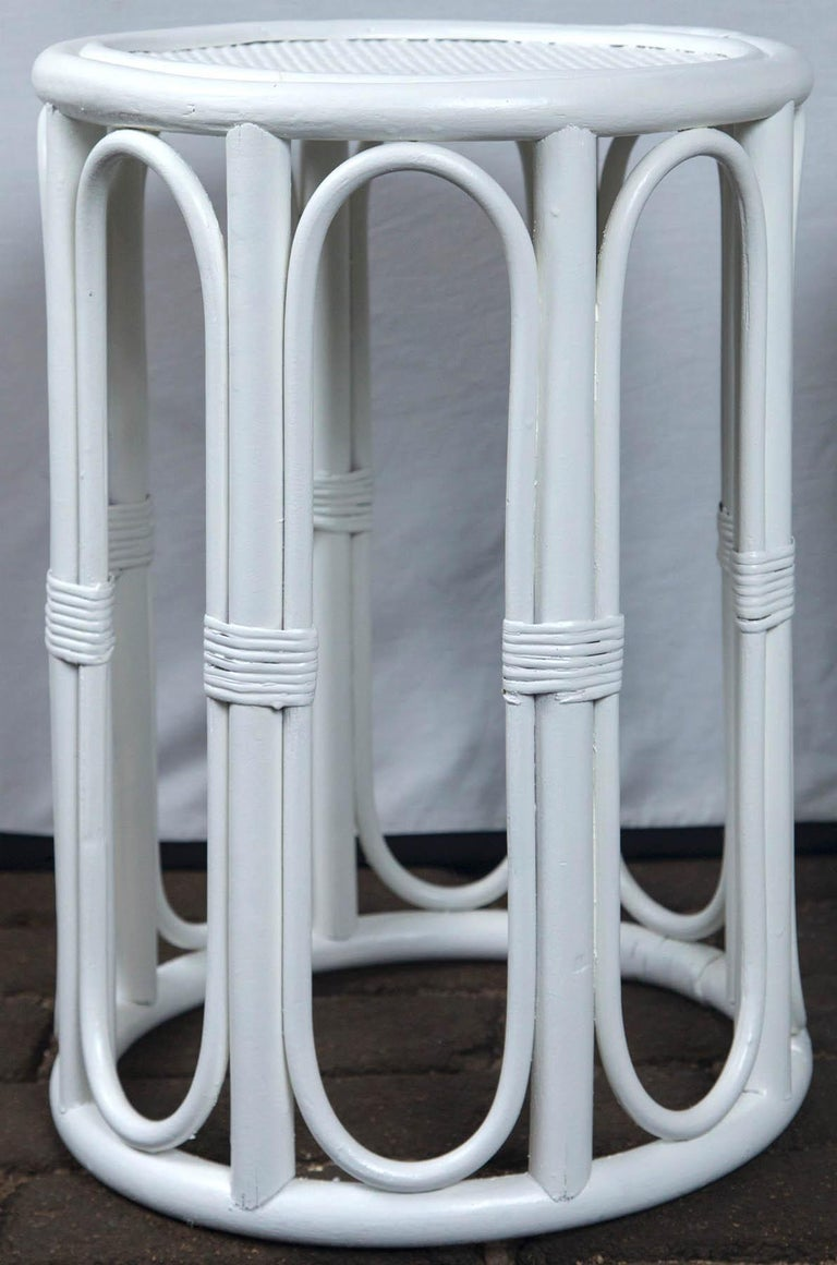 Pair cylindrical white painted rattan side tables.