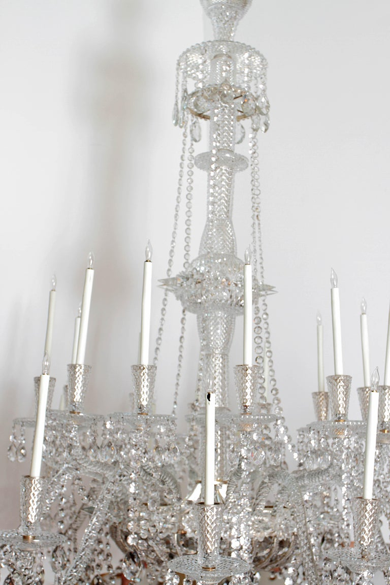 A pair of beautiful grand-scale and well-appointed cut-crystal and silver plate Georgian-style / mid-Victorian chandeliers. 24 imposing candle arms each contain a single white taper. In the crystal basket or bag at base are six lights or bulbs that