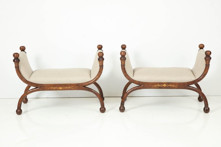 A pair of unusual curved 19th century Biedermeier X benches with ebonized and inlaid decoration. Perfect in front of a window, at the foot of twin beds or as extra seating in a living room. The benches have been recently re-upholstered in a natural