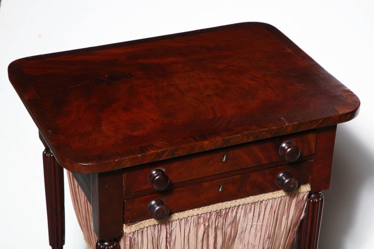 A fine American Federal reed leg mahogany cross banded worktable with fitted top drawer and sewing bag drawer.