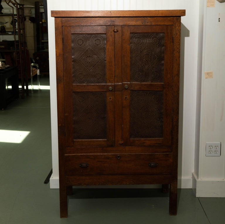 Early 19th century pie safe. Two-door over one drawer, interior two shelves, perforated tin panel doors. Five recessed panels on each side.