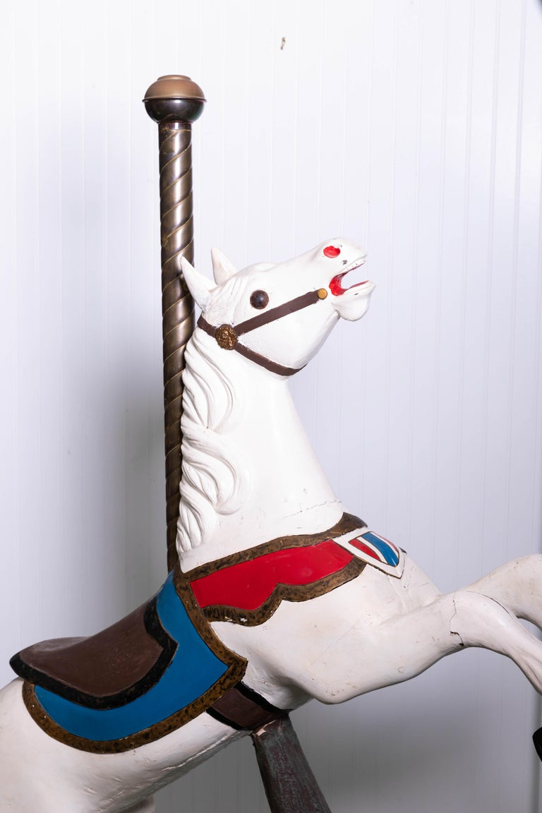 Wooden carousel horse in fixed position. Original gresso over wooden base resembling tree trunk. Horse has been repained while brass pole is an early addition with ears that were replaced.