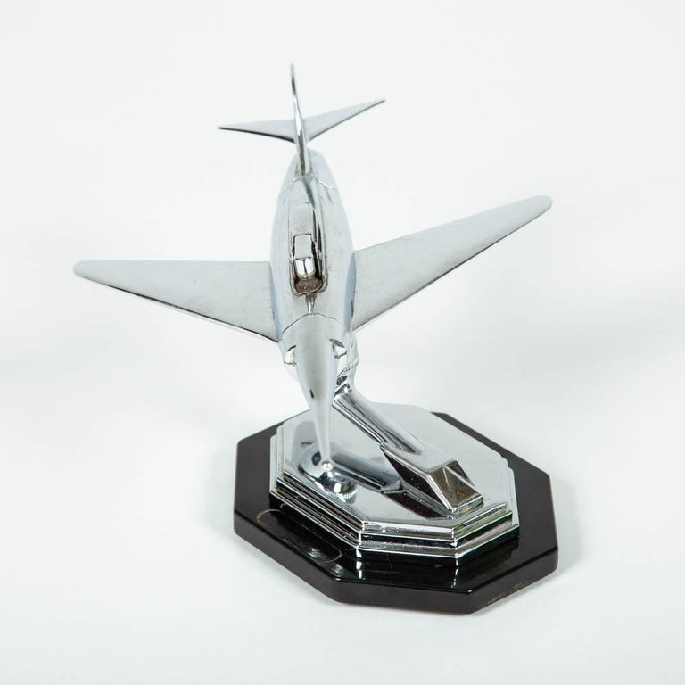 A 1950s chrome jet airplane desk lighter by Gala Sonic of England.   The aircraft moves on a ball joint to angle the lighter.