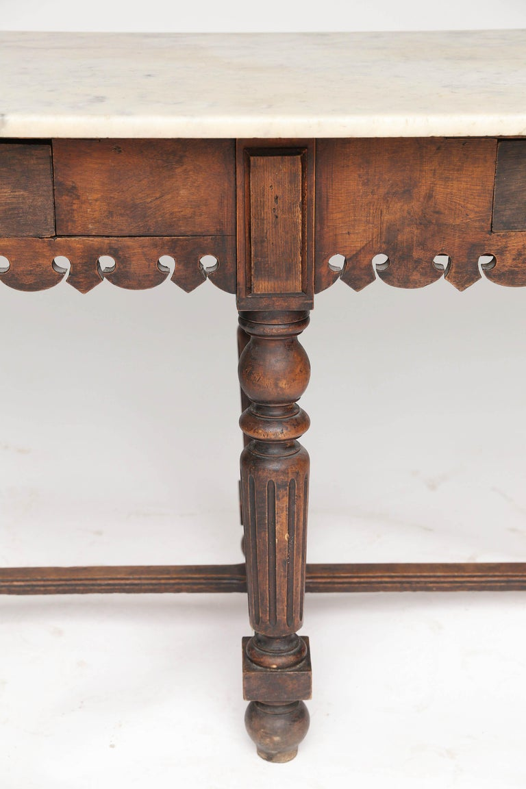 A spectacular antique French marble-top oak butcher table. Featuring an oak base with scalloped apron on both sides and two drawers for storage would make this piece a great addition to any kitchen. The beautiful aged patina marble top gives the