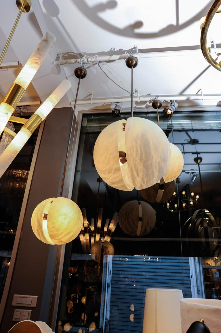 Set of three different sizes suspensions each made of two alabaster half spheres hold together by a brass structure but still leaving a space between the two.  Each suspension can be bought separately, size, color and finitions are customizable.