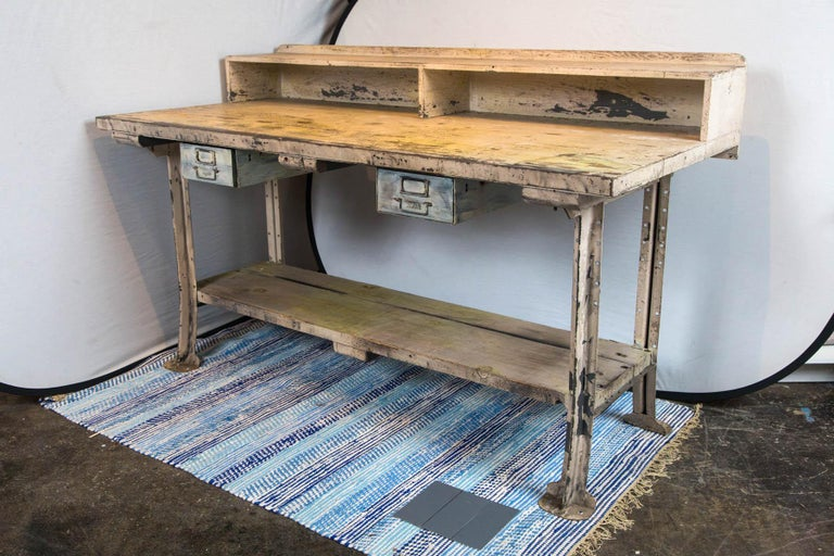 Steel leg wood top workstation with cubbyholes and drawers.