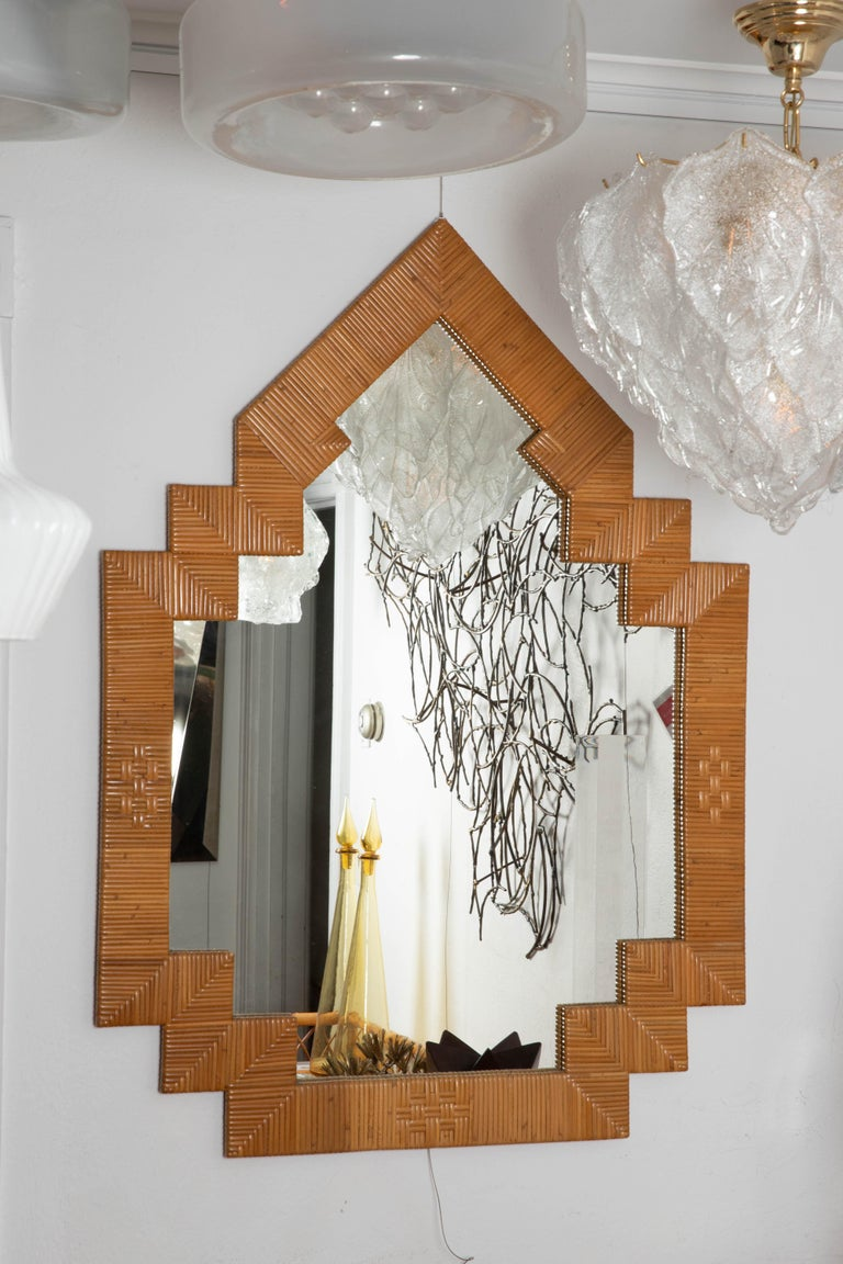 Pair of unusual shaped rattan surround mirrors.