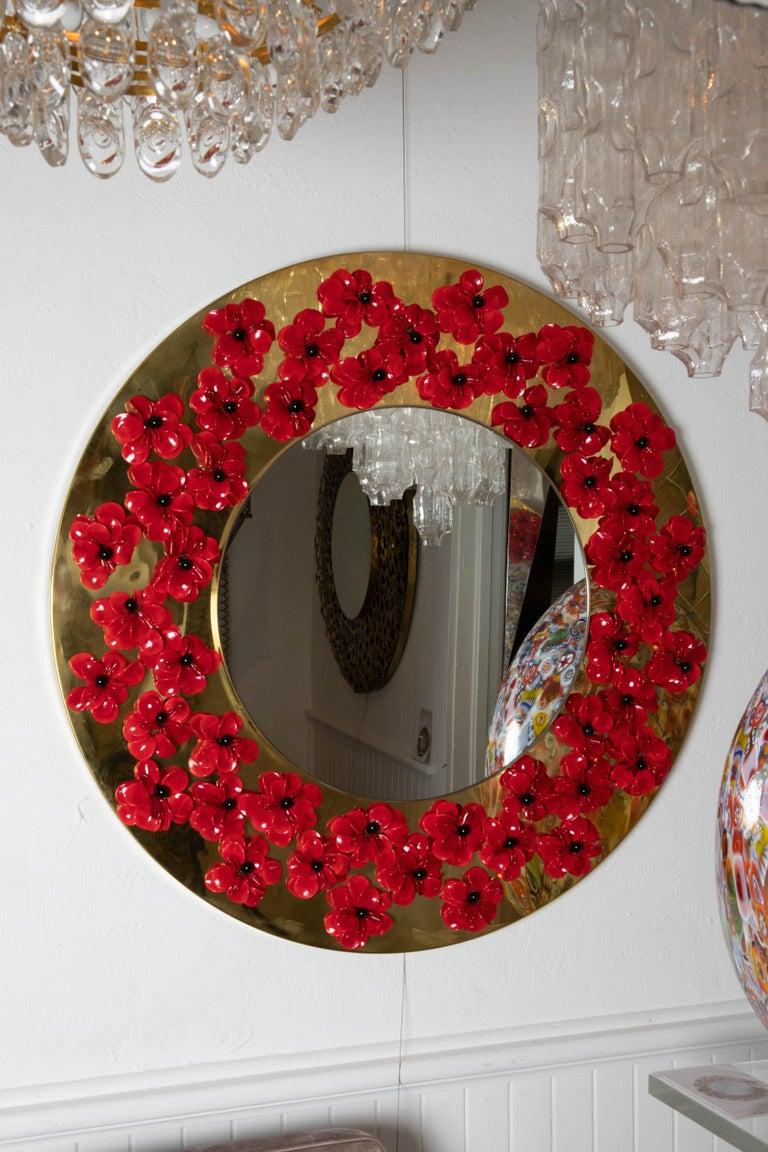 Circular brass mirror with Murano glass flowers.