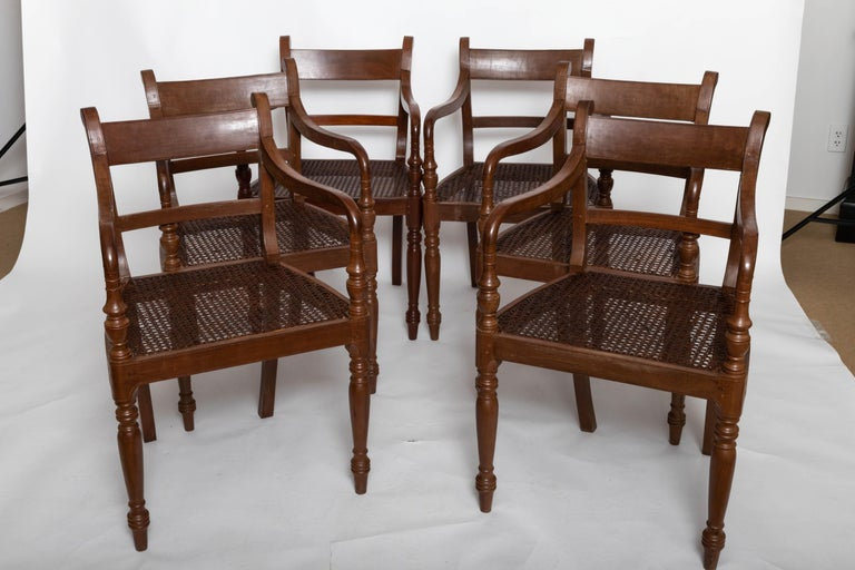 Set of six Ceylonese dining chairs, peg construction, hand carved and hand caned. Solid and very comfortable.