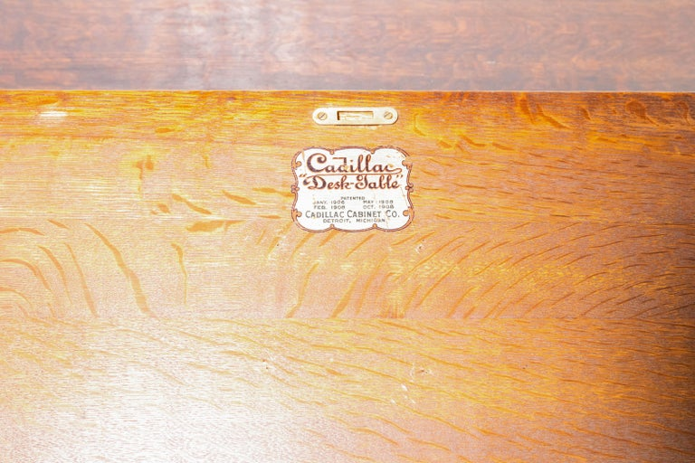 A handsomely crafted Mission writing desk, made of quartersawn oak, by the Cadillac Cabinet Co. patented 1906-1908. The desk has a center drawer with a hidged lid that can be used as a writing surface or for a keyboard, and storage in the drawer for