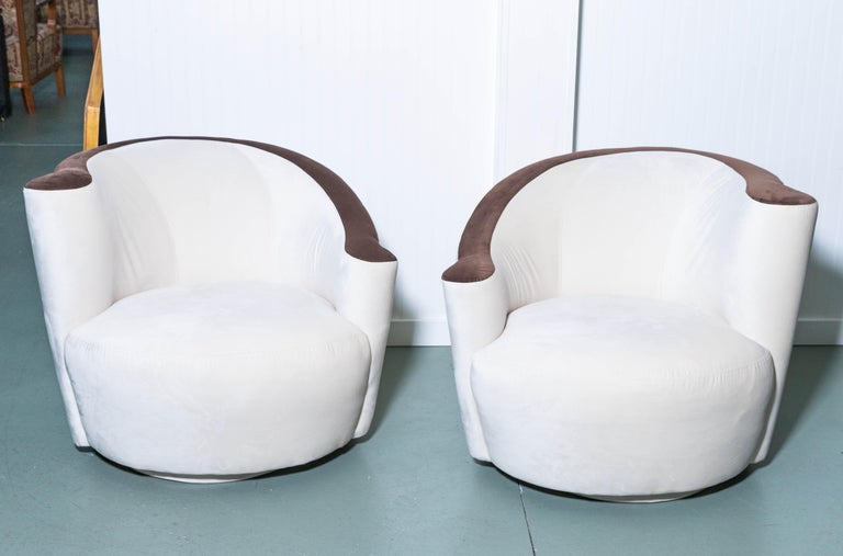 Pair of Vladimir Kagan Nautilus swivel chairs, newly upholstered in cream and chocolate ultrasuede for Weiman. LUX with curved top sides and seat. True deco style.