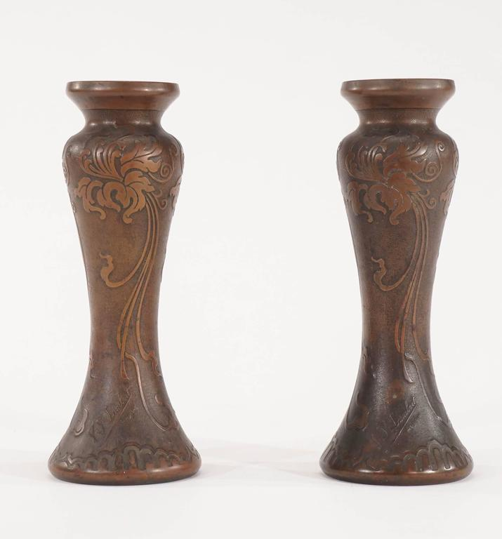 A lovely pair of signed Val Saint Lambert handblown amethyst crystal vases overlaid with a gilded bronze-patina; the body is decorated with a high relief depicting Irises decorated in a pure Art Nouveau swirling motifs. The body has a subtle