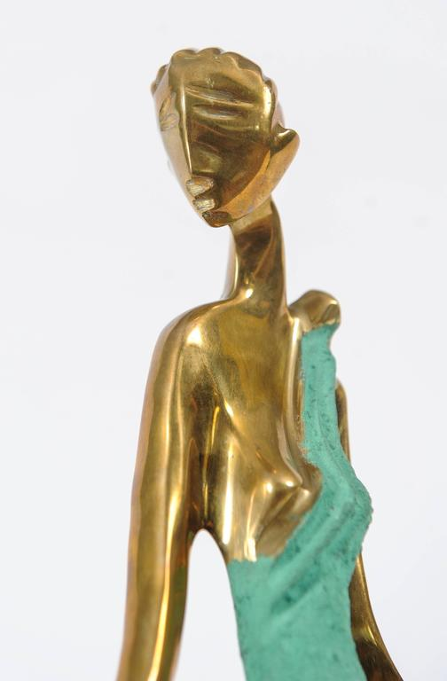 Statuette of an elegantly dressed lady made of brass on a wooden base.