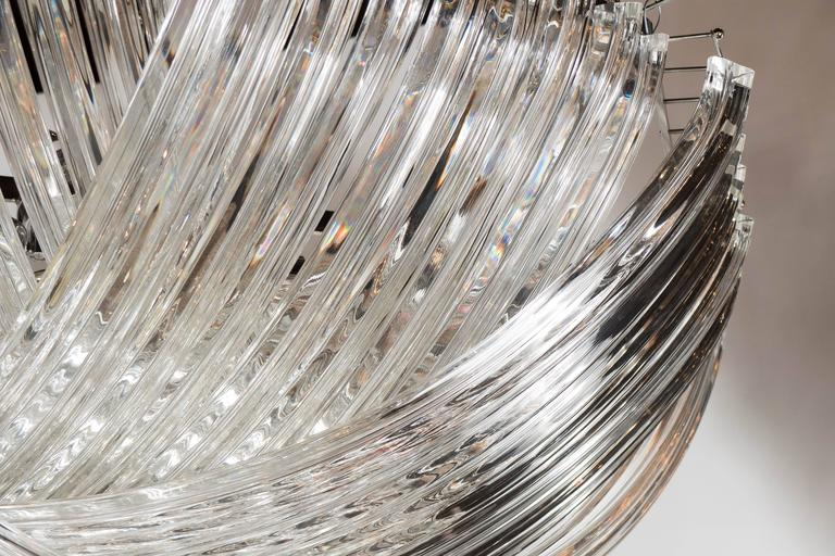 This monumental chandelier is comprised of numerous curved, handblown Murano glass triedre shaped glass rods that are suspended in an overlapping, ribbon-like design, giving this chandelier it's elegant appearance. This ribbon chandelier holds 6