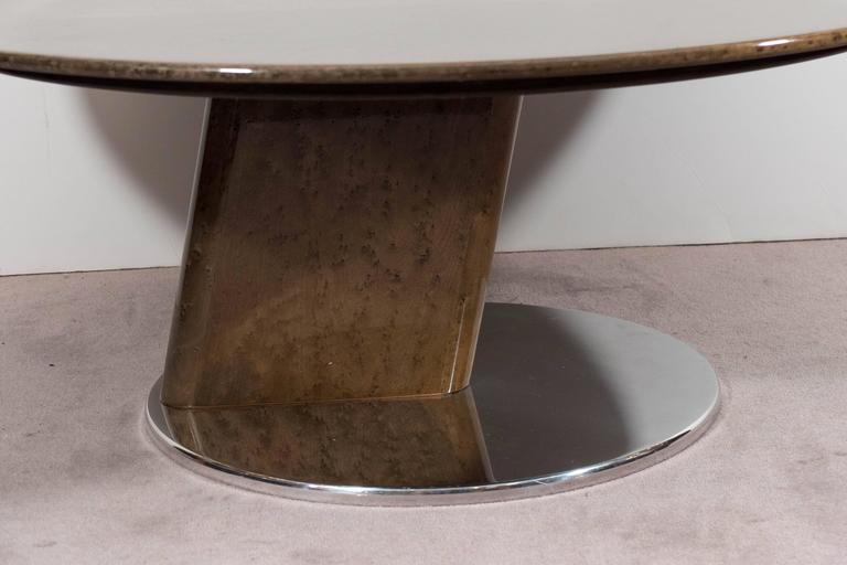 A round, birds-eye maple coffee table by Saporiti, lacquered to a gleaming finish, above a smaller circular polished steel base. The base features a unique triangular shape joining the two circles. Good condition, consistent with age and use, with a