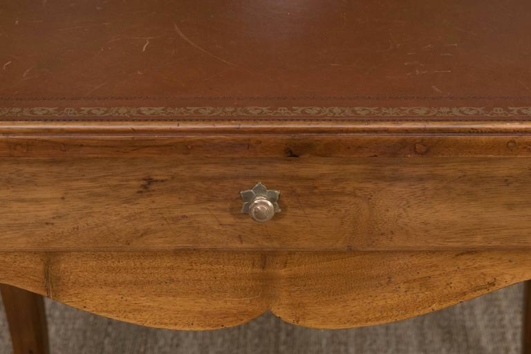 A Louis XV style fruitwood writing table with one drawer and tooled leather top.