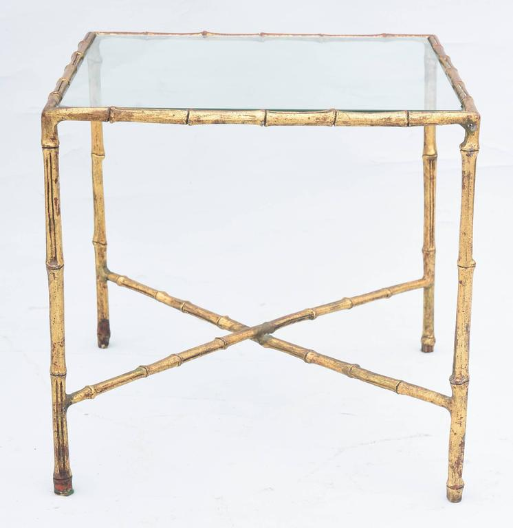 Side table, of gilded iron, its faux bamboo frame, holding a top of clear glass, raised on straight legs, joined by X-stretcher.