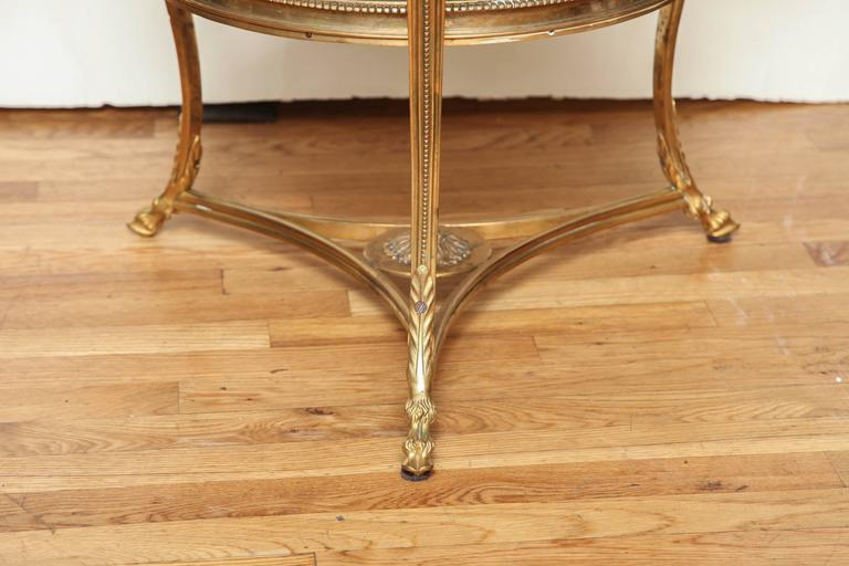 A round French Louis XVI Style two-tiered boulliotte table with black marble surfaces and set in bronze frame with beadwork detail, the three cabriole legs having ram's head detail at the top and split hooved feet below stretcher with large center