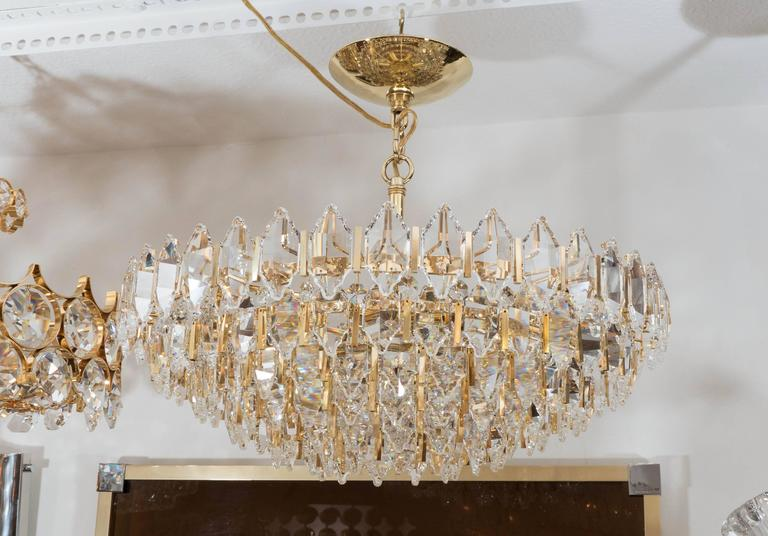 Tiered brass chandelier featuring suspended diamond-shaped, facet-cut crystal elements.