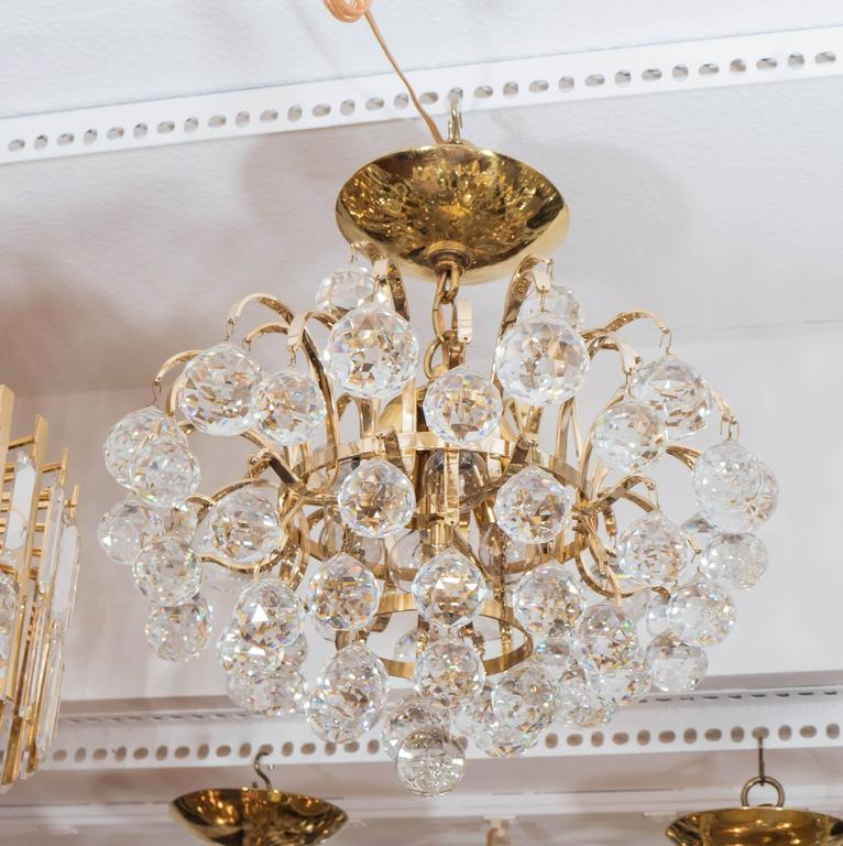 Brass chandelier composed of spherical cut crystal drop elements.
