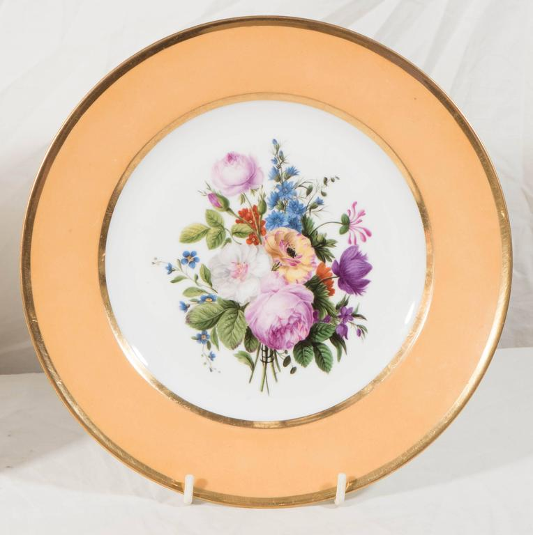 A pair of beautiful Sèvres porcelain dishes each with a hand-painted bouquet of exceptionally well painted flowers in soft pinks, blue, purple, and yellow. The center bouquets are complemented by a rich apricot border. Dimensions: diameter 9.25