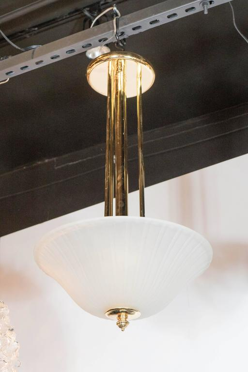This elegant Art Deco pendant consists of a ribbed and fluted frosted glass dome supported by a detailed brass support, which connects to one wide and three supporting polished brass rods which connects to a flush mount cap. The clean lines on this