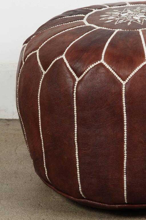 Moroccan handcrafted brown leather ottoman, with embroideries. Could be used as a stool, side table or ottoman. The Moroccan leather poufs are hand-tooled and embroidered with white thread. Very nice handmade Moroccan dark brown color leather