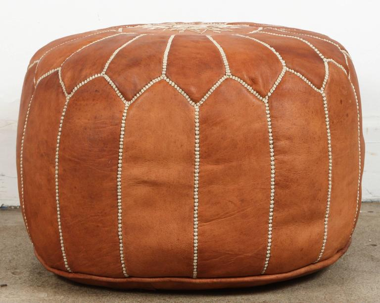 Moroccan handcrafted camel leather ottoman, with embroideries. Could be used a foot stool, or side table or ottoman. The Moroccan leather poufs are hand-tooled and embroidered with white tread. Very nice handmade Moroccan tan camel color leather