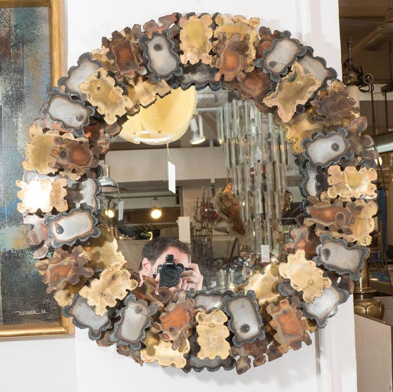 A round wall mirror, with an elaborate frame designed in the manner of Brutalist artist and designer Silas Seandel, decorated with rough and distressed cutouts of mixed metal sheets in three different tones, circa 1970s. Markings include signature,