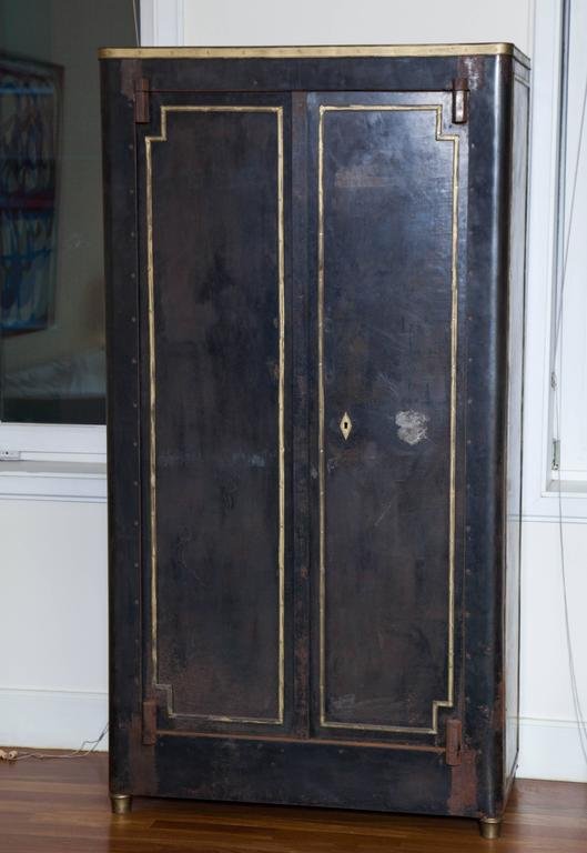 Impressive 20th century French blackened metal armoire with bronze accents and a beautiful patina. Adjustable metal shelving.