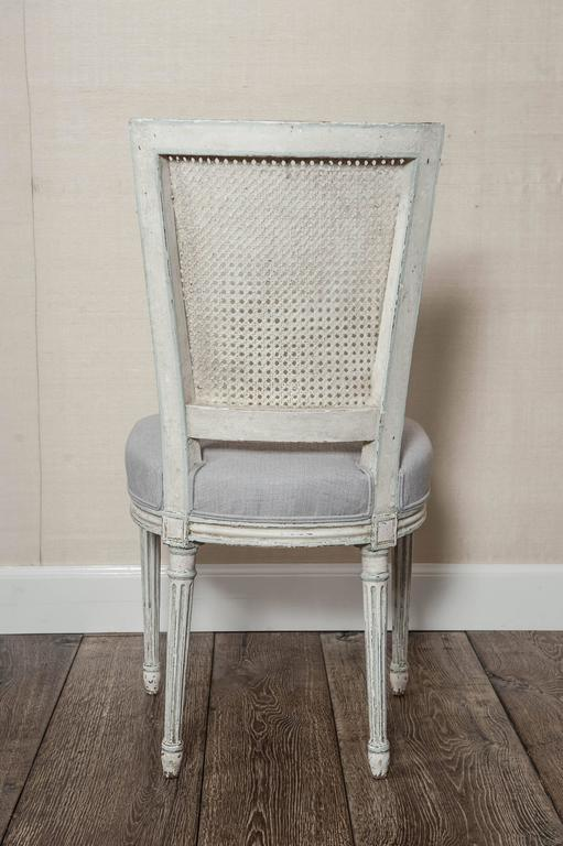 A set of six carved, white painted and (new) linen upholstered French Louis XVI/Seize style dining chairs, 19th century.