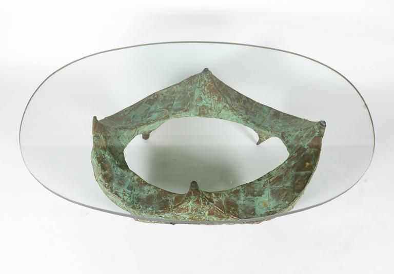A sculptural hand-hammered verdigris copper coffee table with the original 3/4 in glass.