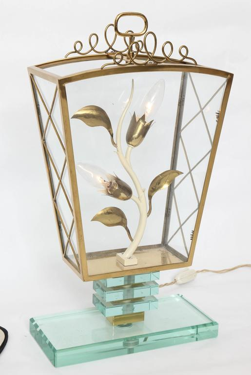 A 1940s Italian art moderne style table lamp in brass and glass, designed in the style of Pietro Chiesa, with curling stylistic stem, including two sockets.