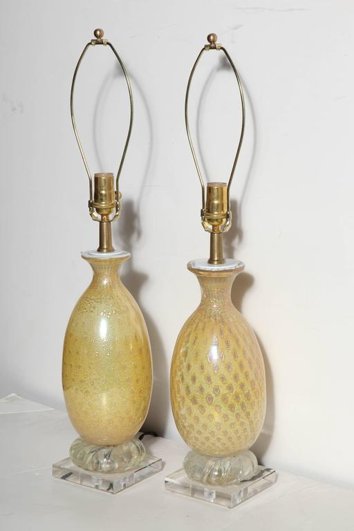 Two Italian Modern Alfredo Barbini style Yellow & White Murano Art Glass Table Lamps. Featuring hand blown bottle forms in White with Silver rimmed Gold inclusions. Brass neck. White cap. With round swirled clear glass detail above square 5H Lucite