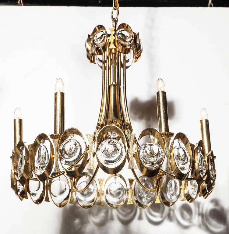 1960s Palwa Gilt Brass and transparent Crystal adjustable Hanging Pendant. Featuring a round gilt Brass ring, six candlesticks and three levels of hanging Austrian crystals. Adjustable height. Subtle. Elegant. Shimmering. Sparkling. Reflective. Made