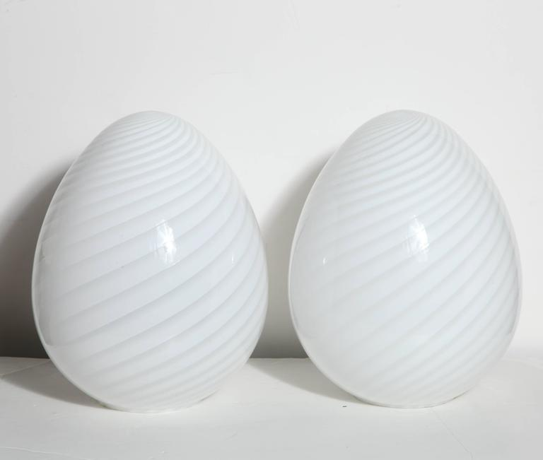 Large Pair of 1970s Itri Vetri Murano Translucent White Art Glass Egg Lamps. Featuring hand blown spiral swirled glass shades.  Radiant. Italian Modern. Rewired since photography. Made in Italy.  Additional shipping methods may be available, please