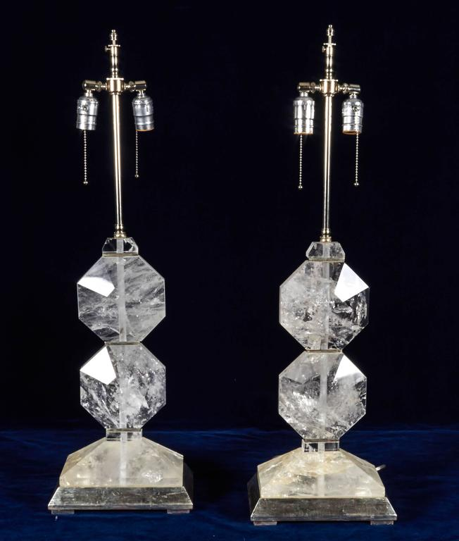 A fine pair of French Art Deco style, hand diamond cut and faceted rock crystal lamps, mounted on rectangular shaped platinum bases. In the style of Maison Jansen.  The height without electrical fitting is 18.5