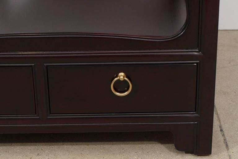Classically styled Mid-Century mahogany end tables with two pull-out drawers with brass ring pulls and sinuous frames. Mint restored with a dark coffee bean color with a slight sheen. Tables are finished on all four sides.