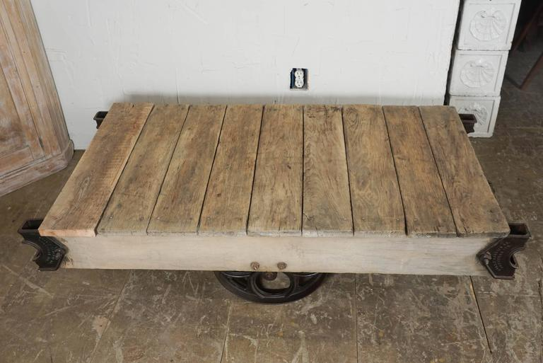 Vintage industrial rustic rolling cart made of wood planks and cast iron wheels and brackets, the loader has two end wheels that swivel and are slightly shorter than the larger sides ones for easier movability.  Cart does sit flat on the ground but