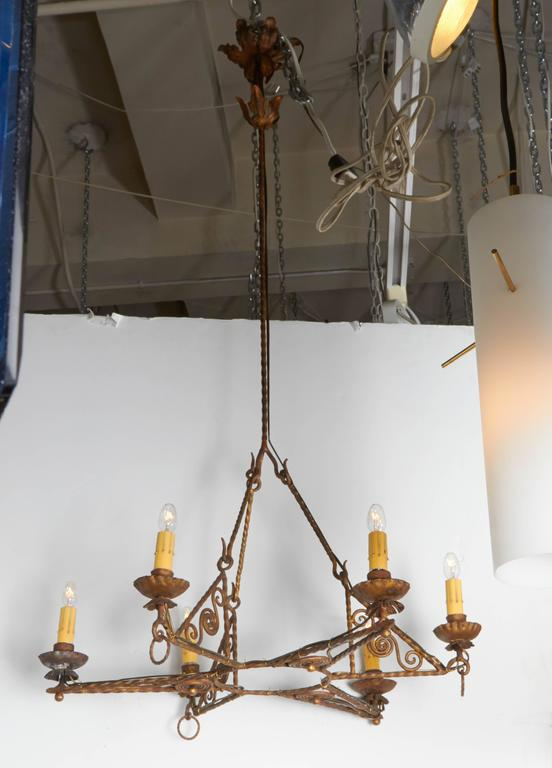 A very nice Italian Art Deco chandelier, circa 1920. Entirely hand-wrought and gilt iron with spiral scroll work accents. Six arms support each candelabra socket with cover in a star design. Externally re-wired in the same manner as found in an